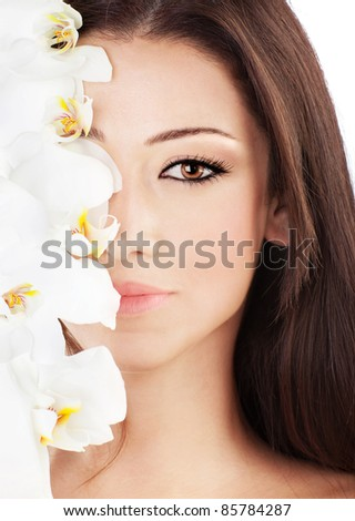 Closeup on beautiful face with white orchid flower, perfect clean skin, young female portrait, beauty and spa concept - stock photo