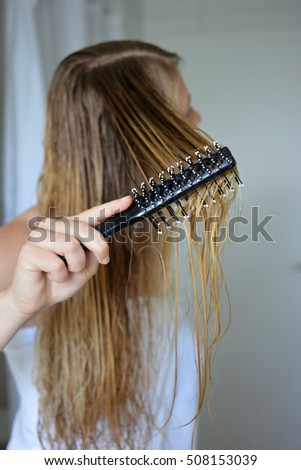 Closeup on blond woman combing hair