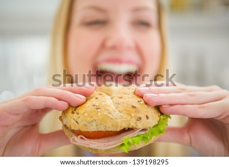 Closeup on burger in hand of smiling teenager girl