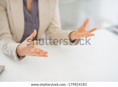 Closeup on business woman explaining something using hands - stock photo