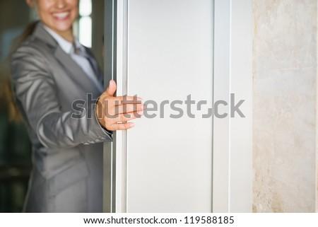 Closeup on business woman hand holding elevator door - stock photo