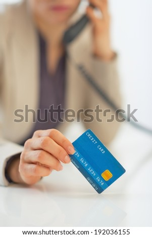 Closeup on business woman with credit card talking phone