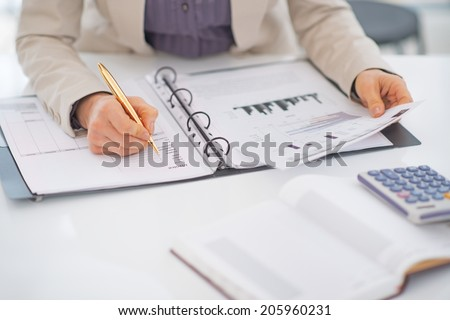 Closeup on business woman working with documents - stock photo