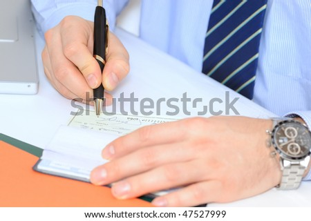 Closeup on businessman`s hands writing a check - stock photo