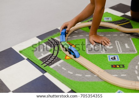 Closeup on children playing with wooden toy train, build railroad on home or school background