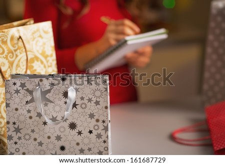 Closeup on christmas shopping bag and woman checking list of presents in background - stock photo
