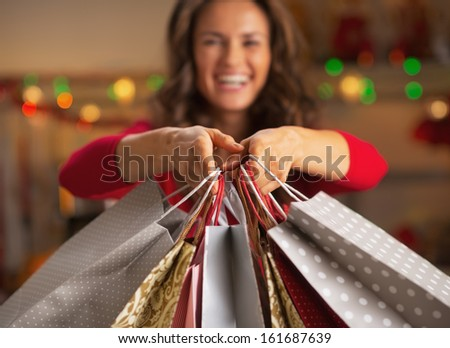 Closeup on christmas shopping bags in hand of smiling young woman - stock photo