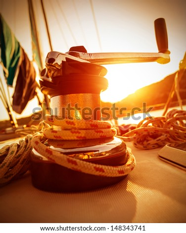 Closeup on crank handle of yacht in warm yellow sunset light, sailboat detail, active lifestyle, water sport, luxury transport, summer tourism concept - stock photo