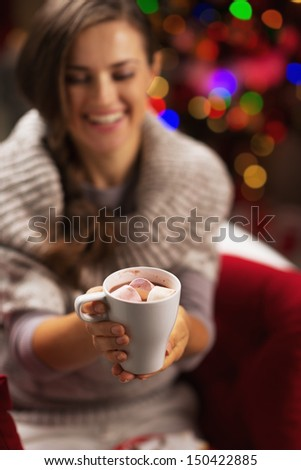 Closeup on cup of hot chocolate with marshmallow in hand of smiling young woman