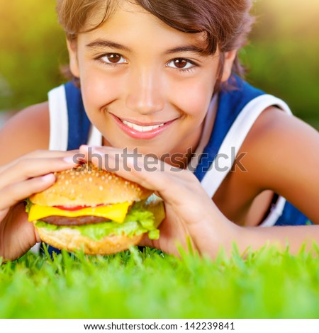 Closeup on cute boy lying down on green grass and eat delicious hamburger, having lunch outdoors, enjoying picnic, healthy food concept
