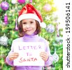Closeup on cute little girl holding in hands letter to Santa Claus, wearing red festive hat, beautiful decorated Christmas tree, winter holidays concept - stock photo