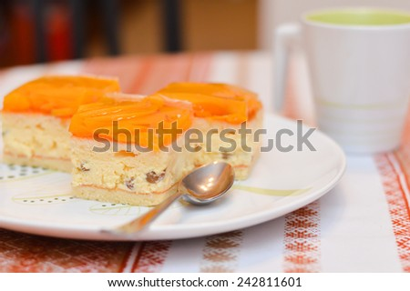 closeup on delicious slice of apricot cake lays on a white plate with a cup of cocoa on the table  - stock photo