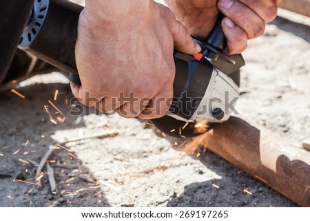 Closeup on electric saw and hands. Man working with grinder, close up on tool and sparks fly