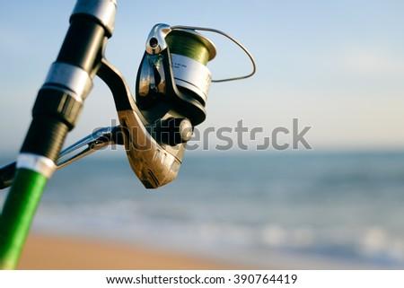 Closeup on fisherman rod on the ocean coast background - stock photo