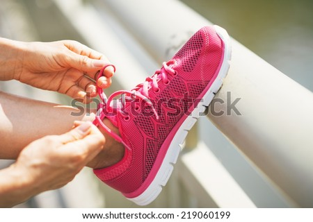 Closeup on fitness young woman tying shoelaces outdoors - stock photo