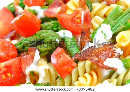 closeup on fusili with tomatoes and asparagus in cream sauce