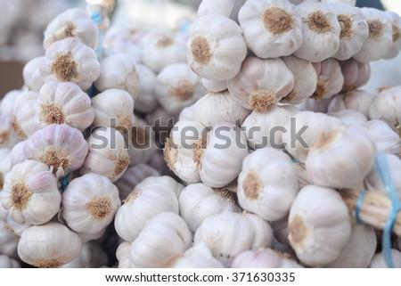 Closeup on garlic in sacks at market or shop. Wholesale business trade - stock photo