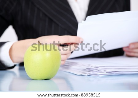 Closeup on green apple lying in the office. - stock photo