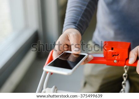 Closeup on hand holding mobile smart phone touch screen with trolley in department store background - stock photo