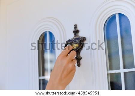 Closeup on hand on beautiful door knocker, elegant design light background - stock photo