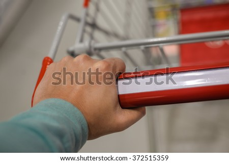 Closeup on hand with shopping cart. Buyer in supermarket