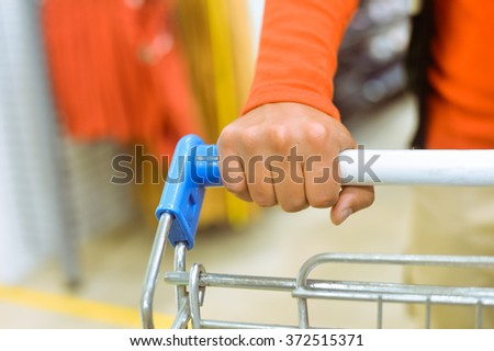 Closeup on hand with shopping cart. Buyer in supermarket - stock photo