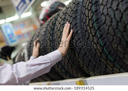 closeup on hands of man or woman touching & choosing for buying a tire in a supermarket shop or DIY department store with shopping shelf on the background - stock photo