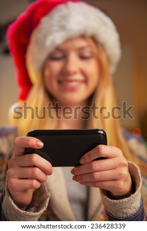 Closeup on happy teenager girl in santa hat writing sms