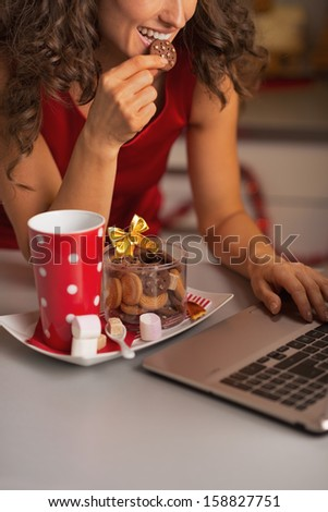 Closeup on happy woman having christmas cookies with cup of hot chocolate and usign laptop - stock photo