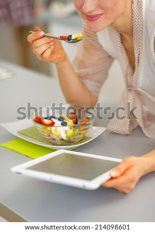 Closeup on happy young woman eating fruit salad and using tablet pc