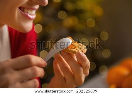 Closeup on happy young woman putting orange jam on cookie - stock photo