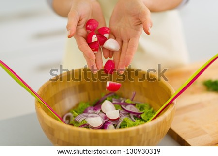 Closeup on housewife adding radishes into vegetable salad - stock photo