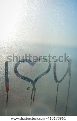 Closeup on I love you sign drawing on fogged window glass background - stock photo
