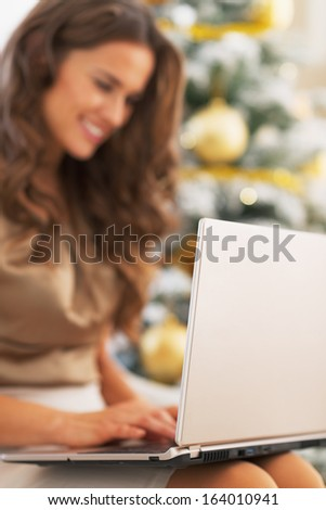 Closeup on laptop used by young woman near christmas tree - stock photo