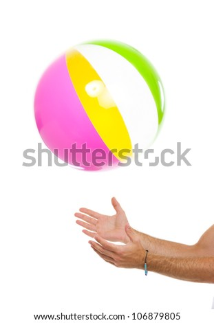 Closeup on males hand throwing beach ball up - stock photo