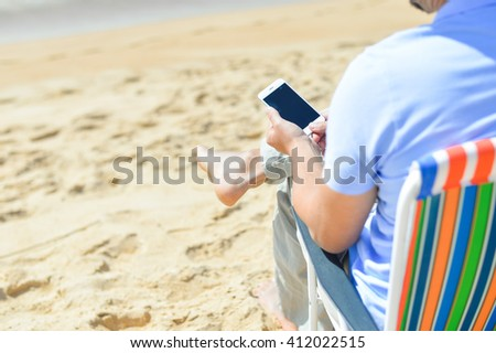 Closeup on man chilling on the beach using smartphone. Back side view of guy enjoying outdoors background - stock photo