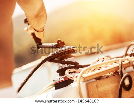 Closeup on man holding crank on the yacht, body part, bright yellow sunset, sailboat detail, active lifestyle, yachting sport, summer relaxation concept - stock photo