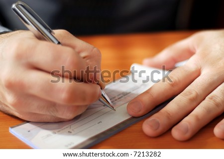 Closeup on man`s hands writing a check - stock photo