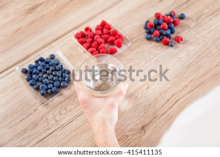 Closeup on man with a glass of water healthy berries on a wooden table - stock photo