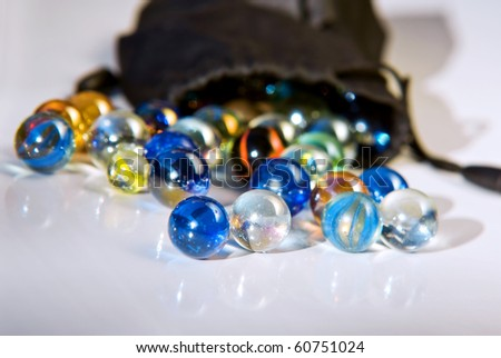 Closeup on many colorful glass marbles on a white surface - stock photo