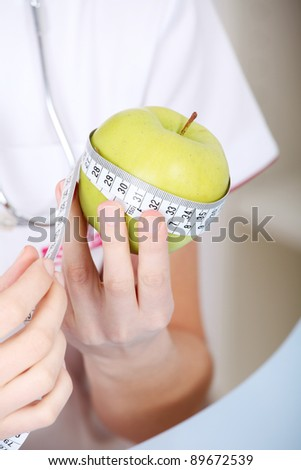 Closeup on measuring apple in caucasian woman`s hands. - stock photo