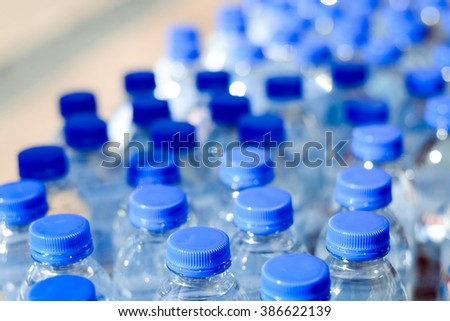 Closeup on mineral water bottles in raw and lines - stock photo
