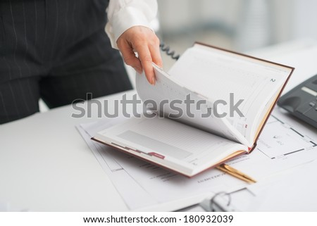 Closeup on modern business woman checking notepad