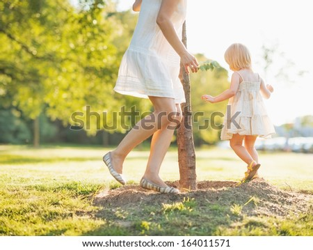 Closeup on mother and baby playing near seedling tree - stock photo