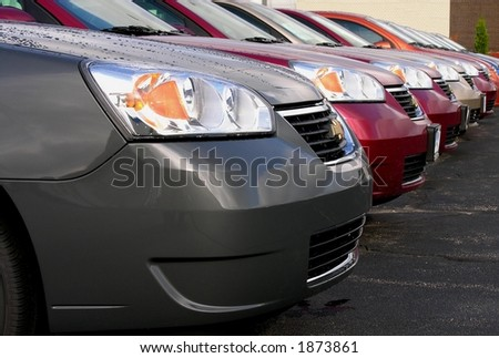 Closeup on new automobiles in dealership lot - stock photo