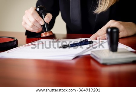 Closeup on notary's public hands stamping document. Notary public accessories - stock photo