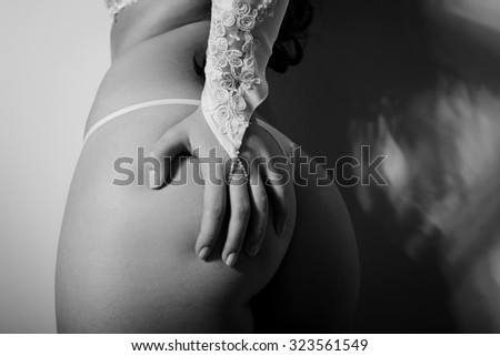 Closeup on perfect sexy buttocks of pretty female in lingerie with hand on butt. Black and white photography - stock photo