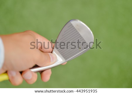 Closeup on person holding golf club in hand, green field background - stock photo