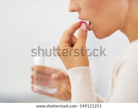 Closeup on pills pack in hand of ill young woman laying on sofa - stock photo