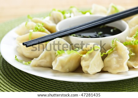Closeup on plate of steamed dumplings with soy sauce and chopsticks - stock photo